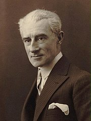 Clean shaven white man with full head of white or grey hair, elegantly dressed