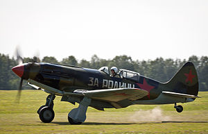 Side view of a piston-engined fighter painted in green and brown with large red star insignia taking off. A slogan in Cyrillic letters is painted on its side.