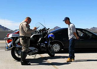 Traffic ticket - A motor officer writes a traffic ticket for a motorist accused of speeding.