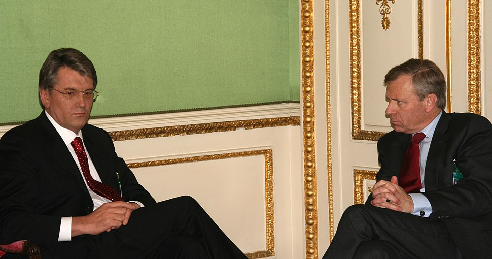 Two older Caucasian men in black suits and red ties sit facing each other in a room with green, white, and gold trimmed walls.