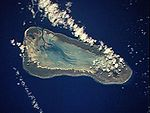 A satellite view of a bare, triangle-shaped island surrounded completely by water.