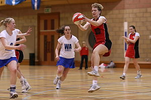 Netball players in centre third of court. One player in red has caught the ball and two players in white are moving towards her.