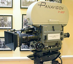 "Clapper loader - Panavision R-200 movie camera (through-the-lens Reflex, 200 degree shutter, hence R-200). The camera magazine is inside the lighter color ""blimp"" on the top of the camera; the camera head is inside the darker color ""blimp"" on the bottom; the camera magazine can be removed to be reloaded by the clapper loader"