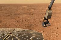 Zdjęcie. Skalista, rdzawa pustynia pod żółtawym niebem. Na pierwszym planie otwarty panel słoneczny i wysięgnik sondy.