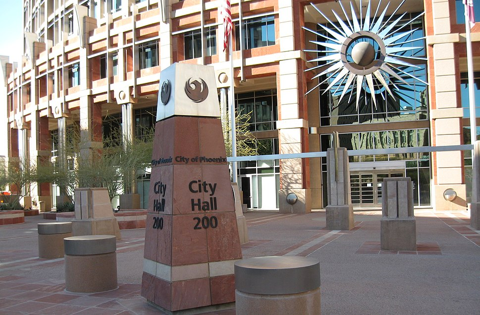 photos showing the short obelisk signage showing City Hall, and topped with the seal of the city, a stylized maroon phoenix.  The semi-circular front of the building in the background, adorned with a stylized sunburst.