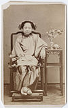 Photograph of a Chinese woman seated with her feet on a stool.jpg