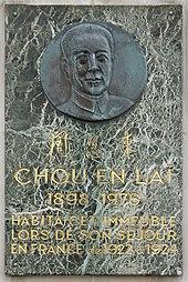 Photographie d'une plaque de marbre portant en haut un buste sculpté sur un médaillon métallique, au centre trois sinogrammes et en bas le texte suivant: «Chou En Laï 1898-1976 habitat cet immeuble lors de son séjour en France de 1922 à 1924».