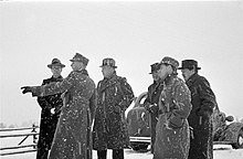 Un grupo de periodistas extranjeros observando algo durante la nevada en Mainila, donde un incidente fronterizo entre Finlandia y la Unión Soviética se convirtió en la Guerra de Invierno.