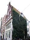 foto van Huis met pilastergevel waarvan de pilasters gehalveerd en de top tot rollagenpunt is afgekloofd