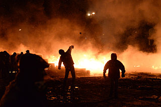 Protesters throwing tires to the fire set by the protesters to prevent internal forces from crossing the barricade line. Kyiv, Ukraine. Jan 22, 2014-5.jpg