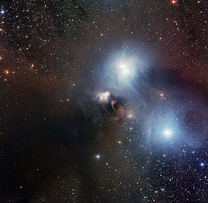 "Corona Australis - The R Coronae Australis region imaged with the Wide Field Imager at ESO's La Silla Observatory. According to ESO, ""The light blue nebulosity seen in this picture is mostly due to the reflection of starlight off small dust particles."" ""A prominent dark lane crosses the image from the centre to the bottom left. Here the visible light emitted by the stars that are forming inside the cloud is completely absorbed by the dust. These objects could only be detected by observing at longer wavelengths, by using a camera that can detect infrared radiation."""