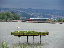SOB Flirt of the S40 line crossing the Seedamm at Rapperswil; Holzbrücke Rapperswil-Hurden in the foreground.