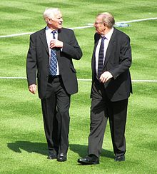Two elderly gentlemen in suits, walking on a football pitch
