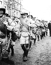 Soldiers in colonial-style military uniforms march past the camera, smiling