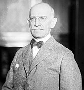 A bald man with glasses wearing a gray jacket and vest, white shirt, and black bowtie