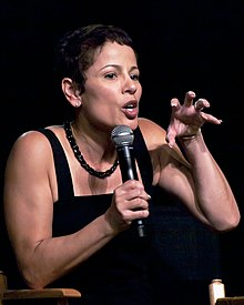 A woman with short brown hair and a black top is talking into a microphone while gesturing with her left hand.