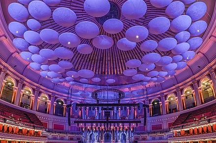 Acoustic diffusing discs (lit in purple/blue) hanging from the roof of the Hall. The fluted aluminium panels are seen behind. Royal Albert Hall - Central View Ceiling.jpg