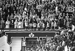 A man stands in the Royal Box lifting a trophy with his teammates walking behind him. A large crowd looks on.