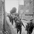 Royal Marine Commandos attached to 3rd Division for the assault on Sword Beach move through Colleville-sur-Orne on their way to relieve forces at Pegasus Bridge, Normandy, 6 June 1944. B5067.jpg