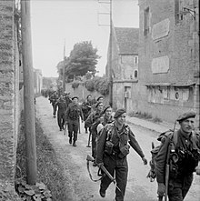 Single file of soldiers walking along a house lined street