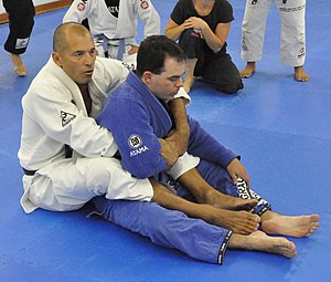 Hooks (grappling) - Royce Gracie (white gi) demonstrates a secure rear mount with hooks on his opponent.