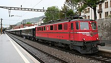 Red locomotive pulling a long passenger train