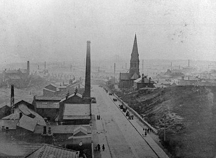 The many chimneys visible in this 1902 picture of the town give an indication as to the degree of industrialisation. The Church of St John is visible here. Stand Lane Radcliffe looking north 1902.jpg