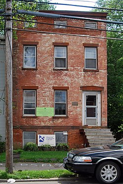 The front of a two-and-a-half story brick building with an exposed basement, seen from a nearby street, partially obstructed by the front of a parked car