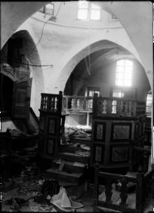 Photo d'archive en noir et blanc de l'intérieur d'une synagogue, avec au sol des traces de saccage.