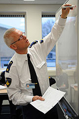 Teacher from Netherlands police academy writing on whiteboard.jpg