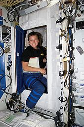 An astronaut emerges from a small sleeping compartment surrounded by equipment.