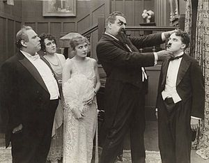 The Adventurer (1917 film) - From left to right are Henry Bergman, Marta Golden, Edna Purviance, Eric Campbell and Charlie Chaplin in a scene still from the film