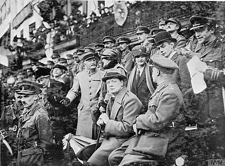Official entry into Lille. The Minister of Munitions, Winston Churchill, watching the march past of the 47th (1/2nd London) Division in the Grande Place, Lille, 28 October 1918. In front of him is the Chief of Staff of the 47th Division, Lieutenant Colonel Bernard Montgomery. The Hundred Days Offensive, August-november 1918 Q11428.jpg