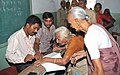 The Polling Officer administering indelible ink at the finger of an old lady during the third phase of General Election-2009, at Dholka, Kheda constituency, in Gujarat on April, 30, 2009.jpg