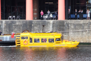 The Queen waves to bystanders from the Yellow Duckmarine, Albert Dock, Liverpool.png