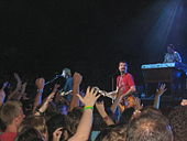 In front of a group of people with arms lifted in the air, two guitarists are playing; a keyboardist is behind them