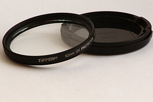 Tiffen - A Tiffen 52mm UV filter resting on a front end lens cap