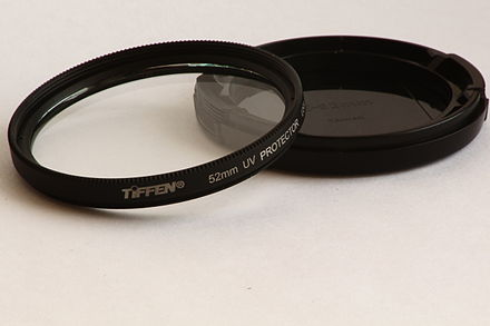 A Tiffen 52mm UV filter resting on a front end lens cap Tiffen 52mm UV filter with lens cap.JPG
