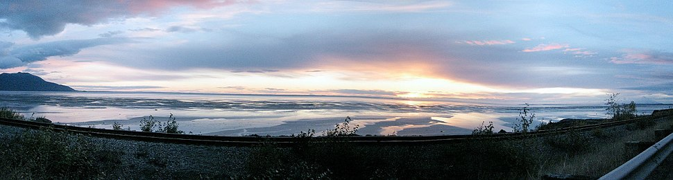 """Panorama of Cook Inlet near the mouth of Turnagain Arm, a few miles south of the """"Anchorage bowl."""" The tide is out, exposing the surrounding mudflats."""