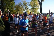 Three women, two smiling, and a man with his hand pointing into the air leading a large group of runners past Lake Calhoun and some observers