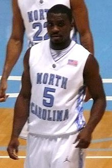 "A basketball player wearing a jersey that reads ""North Carolina""."