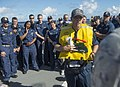 U.S. Navy Boatswain's Mate 1st Class Justin Cox, front, teaches Pacific Partnership 2013 personnel how to use an inflatable life vest during an abandon ship drill aboard the amphibious dock landing ship USS 130529-N-SP369-042.jpg