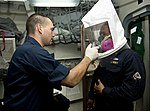 U.S. Navy Quartermaster 1st Class Robert Persi, left, conducts a respirator fit test on Chief Damage Controlman Severino Esteller aboard the guided missile destroyer USS William P. Lawrence (DDG 110) Aug. 30 130830-N-ZQ631-067.jpg