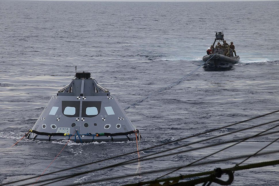 U.S. Navy divers and other personnel in a rigid hull Zodiac boat have attached tether lines to a test version of the Orion crew module during Underway Recovery Test 5 (30660444486).jpg