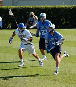jugador de lacrosse masculino corriendo con la pelota