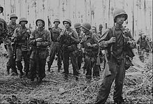 Black and white photo of men wearing military uniforms and carrying rifles standing in front of a dense forest of palm trees