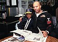 US Navy 030201-N-8770A-001 Information Systems Technician 1st Class Russell Thompson reads a Stars ^ Stripes newspaper to his son in the ship's library during a Family ^ Friendship Cruise.jpg