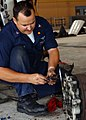 US Navy 041116-N-5152P-004 Aviation Structural Mechanic 2nd Class Chad Albee of Macomb, Okla., removes old caps from the brake assembly of a P-3C Orion.jpg