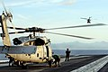 US Navy 080701-N-5961C-004 An SH-60F Seahawk flies off in the distance as crewmen and maintenance crews assigned to Helicopter Anti-Submarine Squadron (HS) 4 prepare a second helicopter for launch from the aircraft carrier USS.jpg
