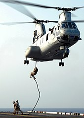 Marines descending from a helicopter with no equipment other than a rope